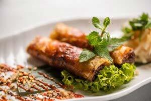 zwei gold-gebackende Rollen mit Hühnerhack, Gemüse mit Limetten Fischsoße, dazu frische Minze